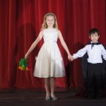 Girl and boy perform on stage.